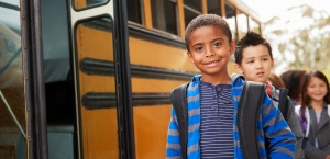Boy standing alongside school bus outside with children in the background.